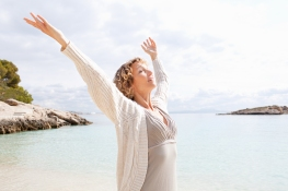 Side view of a healthy senior woman in a transparent beach shore contemplating the sea, breathing raising open arms on sunny holiday destination beach, outdoors. Travel and lifestyle, vacation exterior.