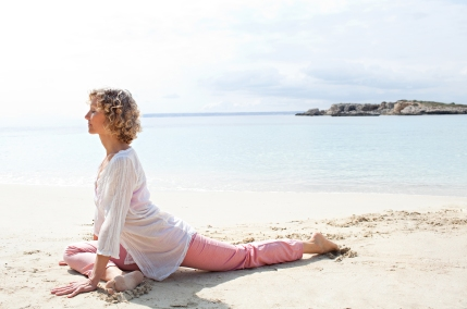 Side view of a healthy senior woman stretching in yoga position, meditating on the shore of a transparent sea in a coastal beach destination, sunny outdoors. Sporty travel lifestyle, spacious nature exterior.