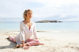 Healthy senior woman stretching in yoga position, meditating on the shore of a transparent sea in a coastal beach destination with eyes closed, sunny outdoors. Sporty travel lifestyle, spacious nature exterior.