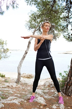 Mature healthy woman stretching her arms, exercising in a coastal nature destination with trees, rocks and the sea, figure outdoors. Wellness and fitness lifestyle, senior woman athlete discipline and effort.