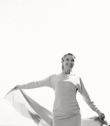 Black and white portrait of mature woman by the sea smiling rasing a floating fabric on a sunny holiday destination, outdoors. Senior healthy woman enjoying the sun, active fun lifestyle.